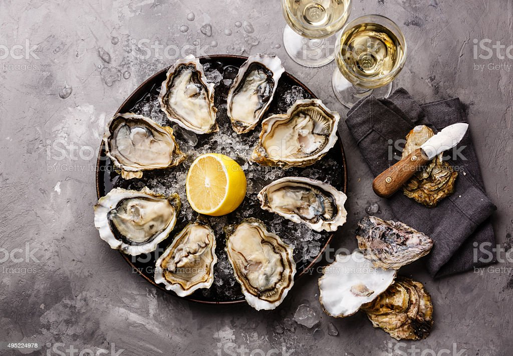 Opened Oysters Fines de Claire and white wine stock photo