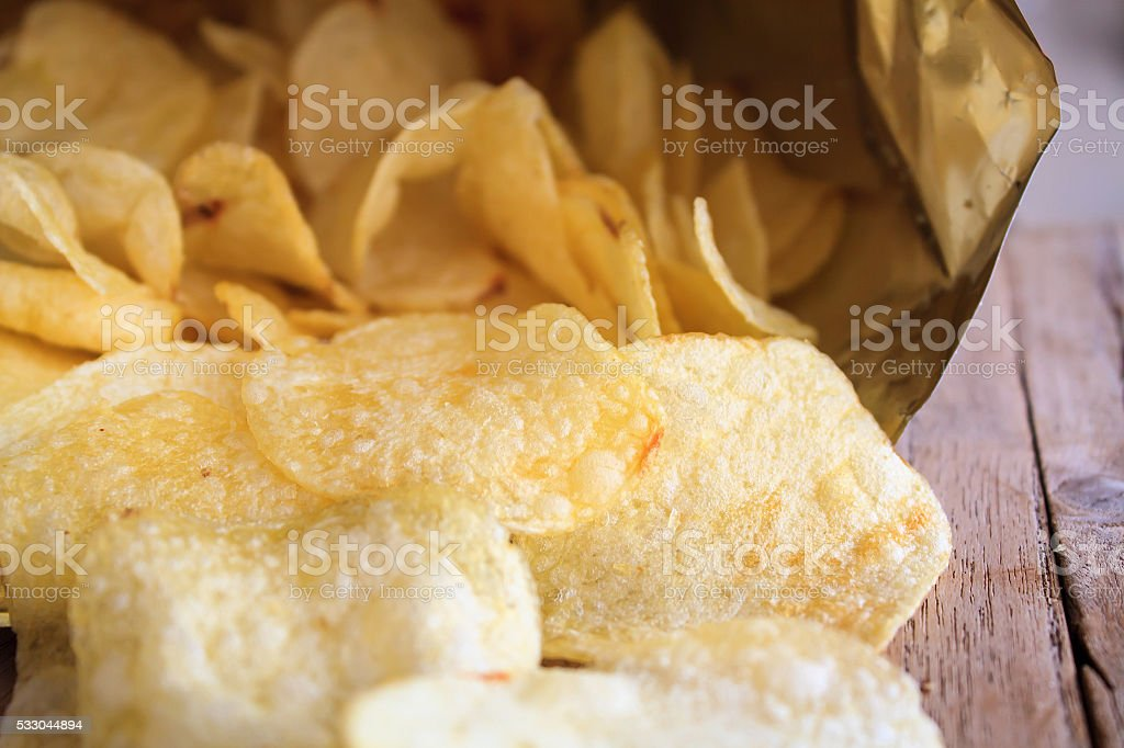 Opened pack of delicious potato chips on wood table stock photo
