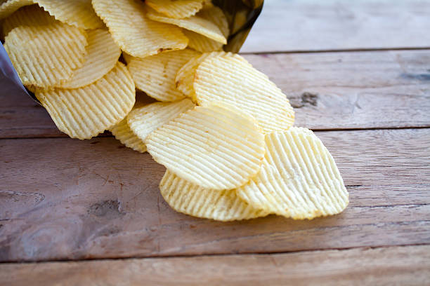 opened pack with potato chips over wooden table - crisp packet stock photos and pictures