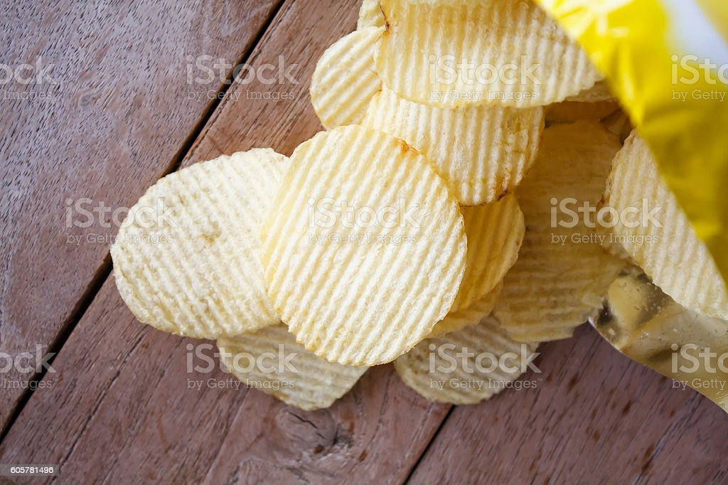 Opened pack with potato chips over wooden table stock photo