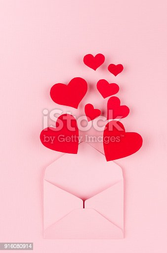 istock Opened paper envelope with red hearts as love message on soft pink color background. Valentine day concept for design. 916080914