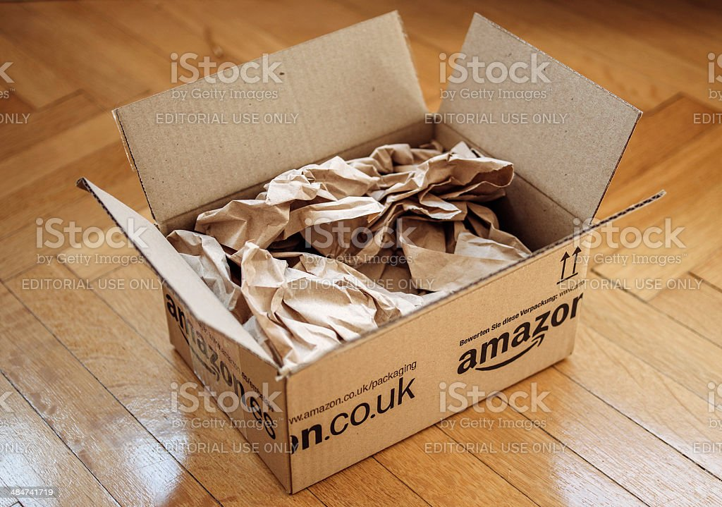 Opened parcel from Amazon on home parquet floor stock photo