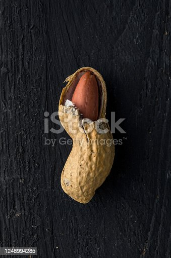 Opened Peanut Shell with a Seed Inside It, on a Black Wooden Surface