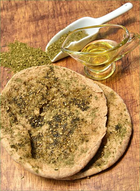 Opened Pita bread with olive oil and Za'atar Pita bread with olive oil and Za'atar-Za'atar  is a generic name for a family of related Middle Eastern herbs from the genera Origanum (Oregano), Calamintha (Basil thyme), Thymus (typically Thymus vulgaris, i.e., Thyme), and Satureja (Savory). The name za'atar alone most properly applies to Origanum syriacum. It is also the name for a condiment made from the dried herb(s), mixed with sesame seeds, dried sumac, and often salt, as well as other spices. Used in Arab cuisine, both the herb and spice mixture are popular throughout the Middle East zaatar spice stock pictures, royalty-free photos & images