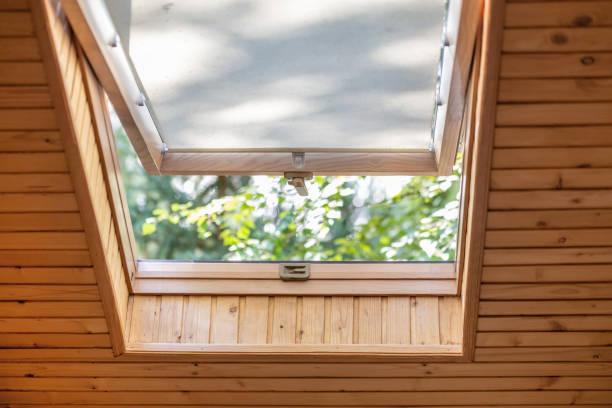 geöffnete dachfenster mit jalousien oder vorhang im holzhaus dachboden. zimmer mit dachschräge natürlichen öko-materialien und blick auf den park durch geöffnete fenster gemacht. haus der umwelt freundlich - dachschräge einrichten stock-fotos und bilder