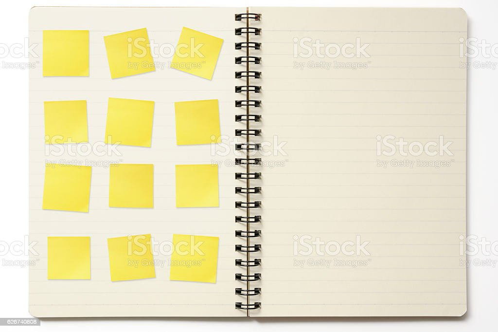 Overhead shot of opened spiral notebook with blank yellow sticky...