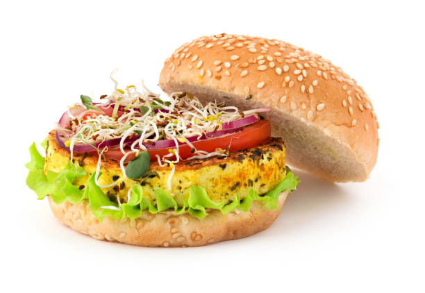Opened vegan burger with grilled tofu cheese, vegetables and micro greens isolated on white background