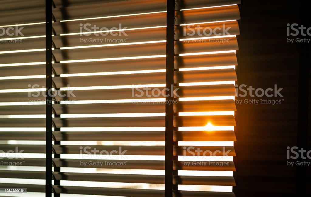 Abre persianas venecianas de plástico con luz del sol en la mañana. Ventana de plástico blanco con persianas. Diseño de interiores de sala con persianas horizontales. Cortinas de ventana de rejilla de plástico. - Foto de stock de Abierto libre de derechos