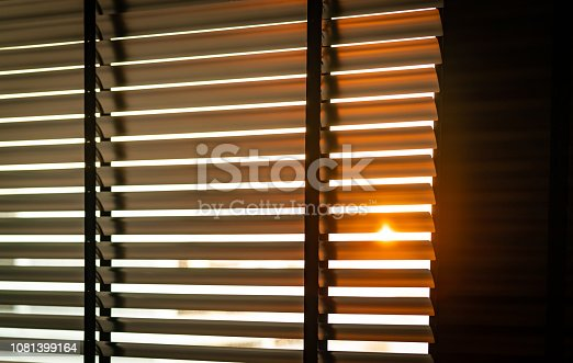 istock Opened venetian plastic blinds with sunlight in the morning. White plastic window with blinds. Interior design of living room with window horizontal blinds. Window slatted shades made of plastic. 1081399164