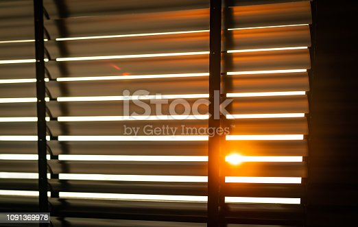 istock Opened venetian plastic blinds with sunlight in the morning. White plastic window with blinds. Interior design of living room with window horizontal blinds. Window slatted shades made of plastic. 1091369978