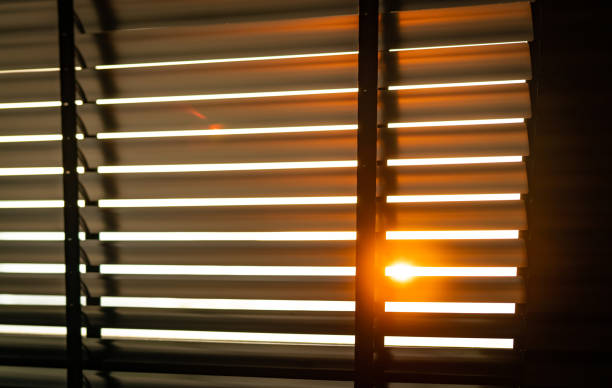 opened venetian plastic blinds with sunlight in the morning. white plastic window with blinds. interior design of living room with window horizontal blinds. window slatted shades made of plastic. - blinds stock pictures, royalty-free photos & images