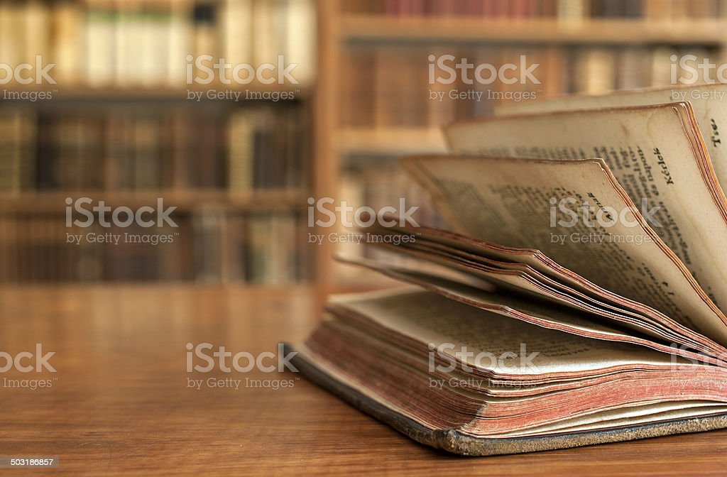 Opened vintage book in a library stock photo