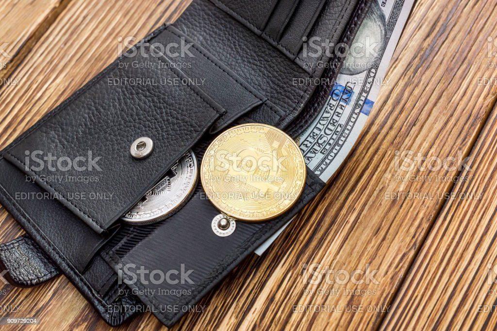 Opened wallet with coins of bitcoin and dollars on the table. stock photo