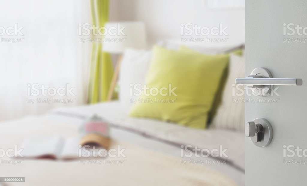 opened white door to bedroom with green pillow on bed royalty-free stock photo