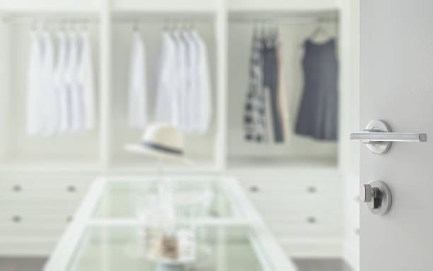opened white door to walk in closet room - schlüssel dekorationen stock-fotos und bilder