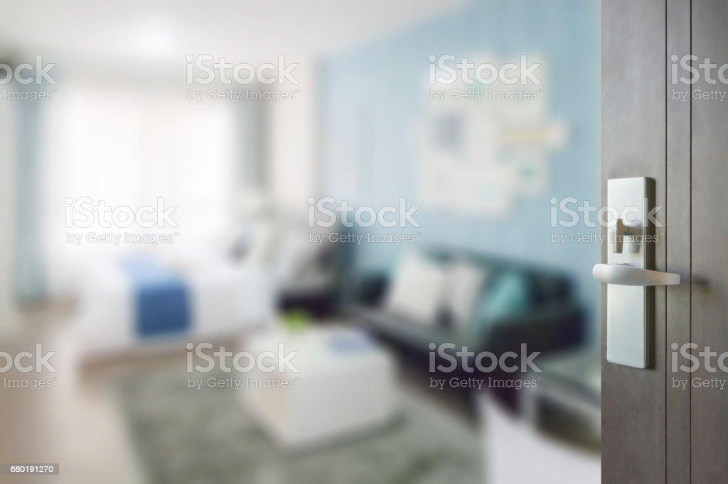 opened wooden door to blue color scheme bedroom with sofa stock photo