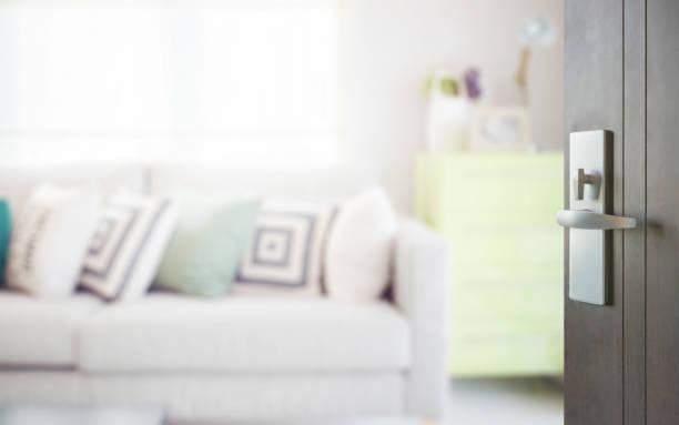 holztür, gemütliches sofa eröffnet mit geometrischem muster kissen und grüne sideboard im wohnbereich - schlüssel dekorationen stock-fotos und bilder