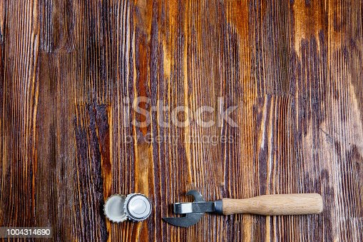istock Opener and lids from beer on a wooden table. Frame. Free place 1004314690