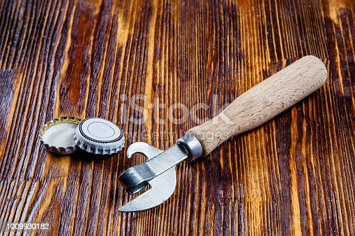 istock Opener and lids from beer on a wooden table. Frame. Free place 1009930182