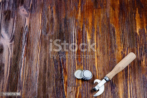 istock Opener and lids from beer on a wooden table. Frame. Free place 1010079780