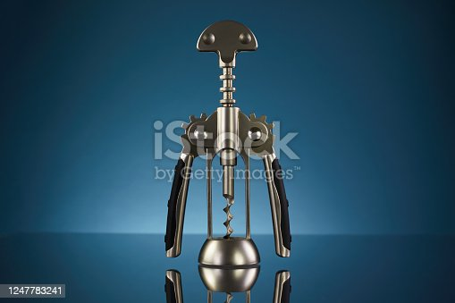 Set of openers and corkscrews inside wooden decorate box isolated on blue background