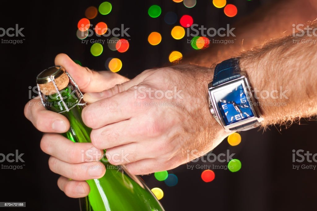 Opening a bottle of sparkling wine like champagne, a man's hand with a watch, New Year's lights, happy new year and Christmas, celebration 2018 stock photo