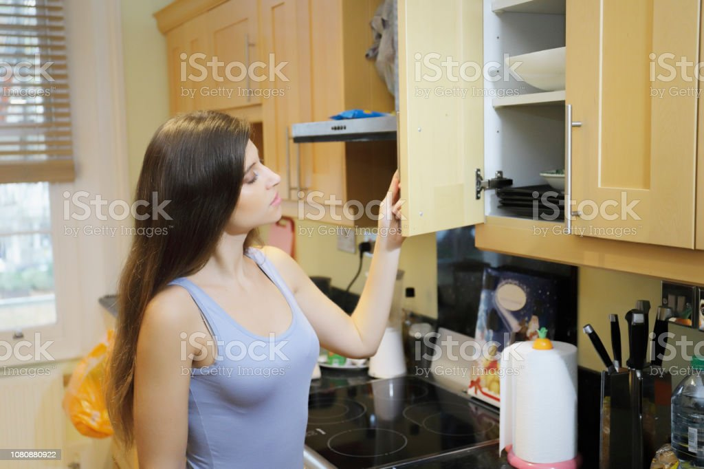 Opening a kitchen cupboard beautiful Russian indoor girl stock photo