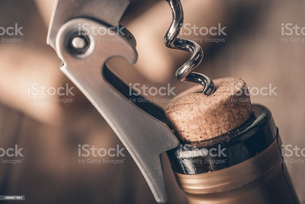 Opening a wine bottle with a corkscrew in a restaurant stock photo