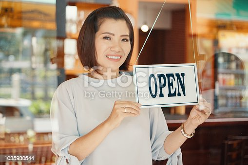 Portrait of pretty Asian female small business owner opening bar