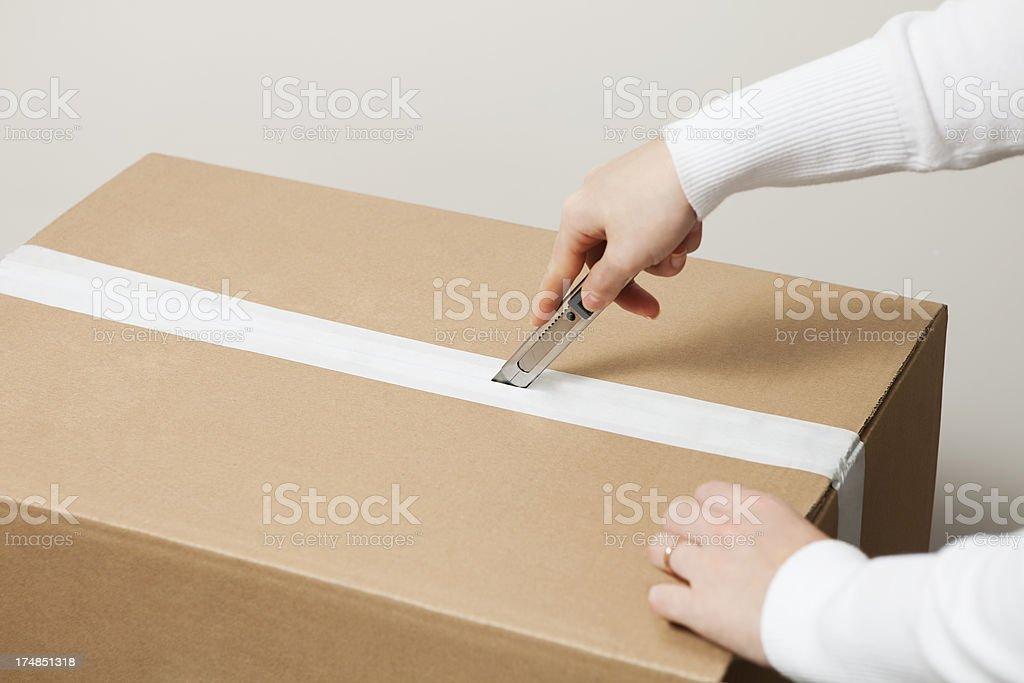 opening box with utility knife stock photo