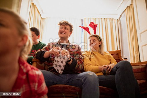Young people are sitting together in the living room at a house party, opening Christmas presents.