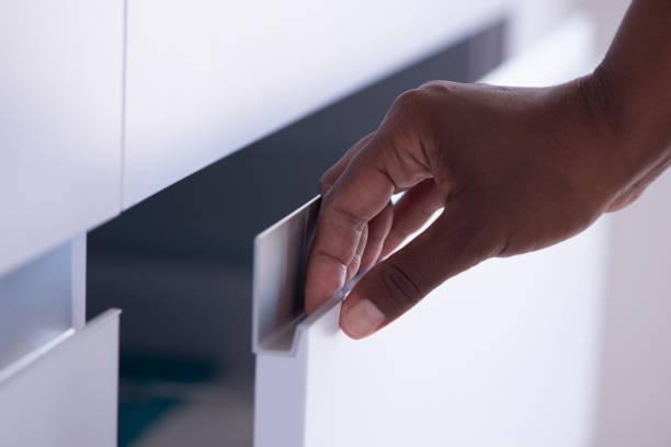 Opening / closing cabinet door. Female's hand holding drawer door aluminum handle. stock photo