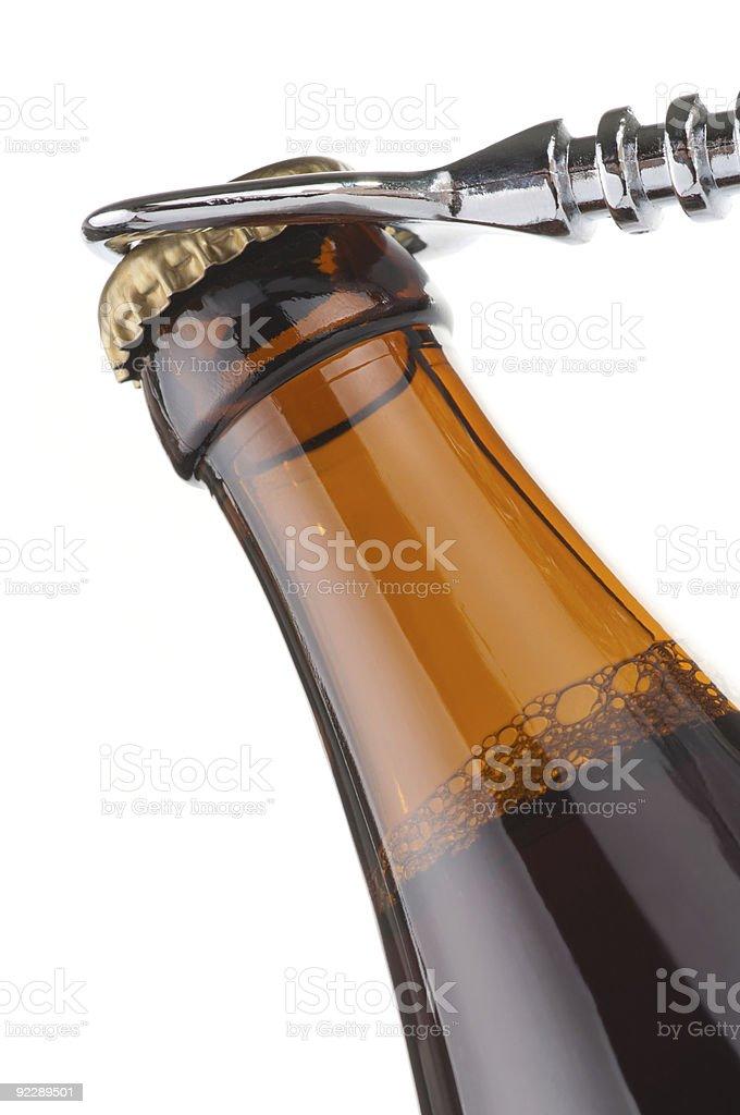 Opening dark beer bottle with metal opener stock photo