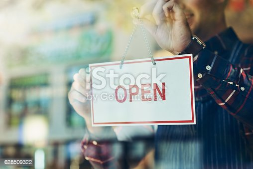 Closeup shot of a young man hanging up an open sign in a shop window