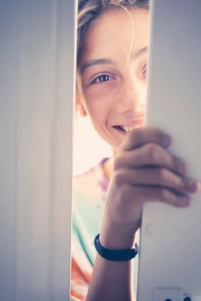 opening door concept with beautiful caucasian blonde young teenager entering the door at home like a guest. smile and cheerful people at home. - going inside eye imagens e fotografias de stock