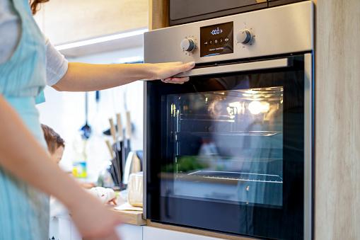 Unrecognizable woman opening door on built in oven