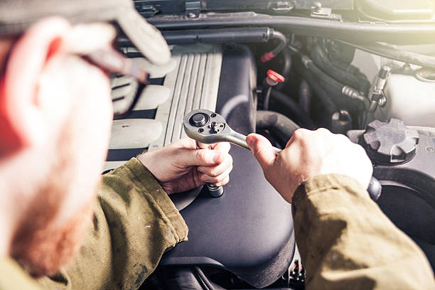 Opening Engine Cover Man Opening Plastic Engine Cover With Ratchet socket wrench stock pictures, royalty-free photos & images