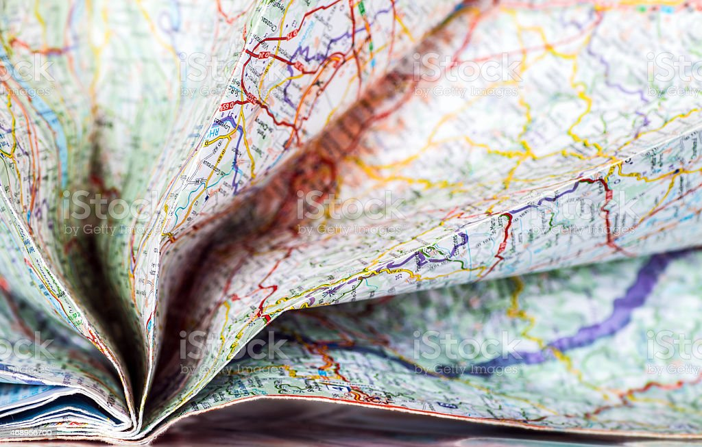 Opening folded colorful map abstract background in selective focus stock photo