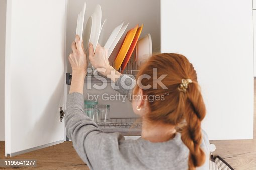 Opening kitchen cabinet door, woman putting plates into it