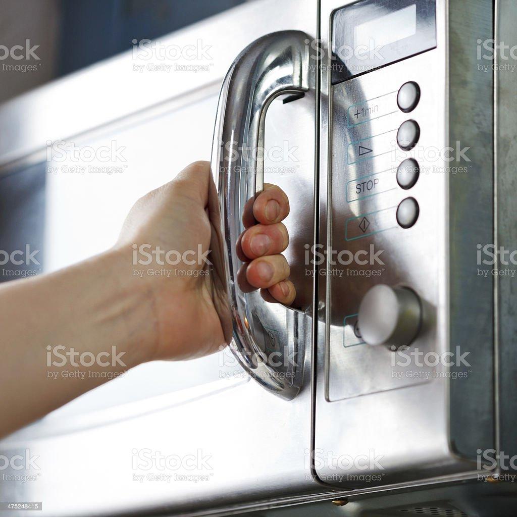 opening of microwave oven door stock photo