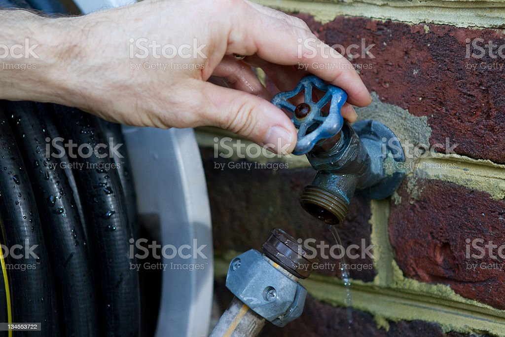 Opening outside water faucet for freeze protection. stock photo