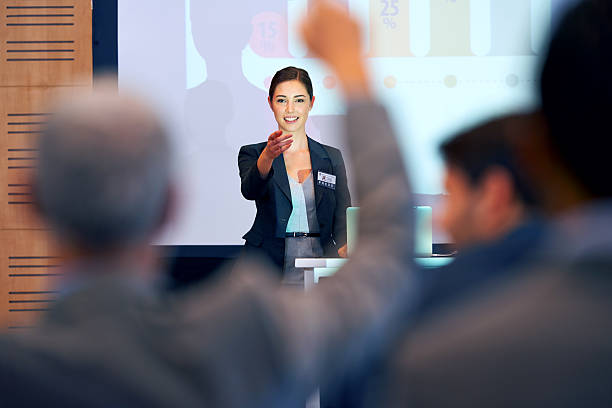 Opening the floor for questions A portrait of a businesswoman gesturing while giving a presentation at a press conference spokesperson stock pictures, royalty-free photos & images