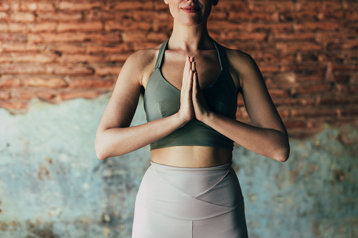 Anonymous woman in sportswear doing yoga at home.