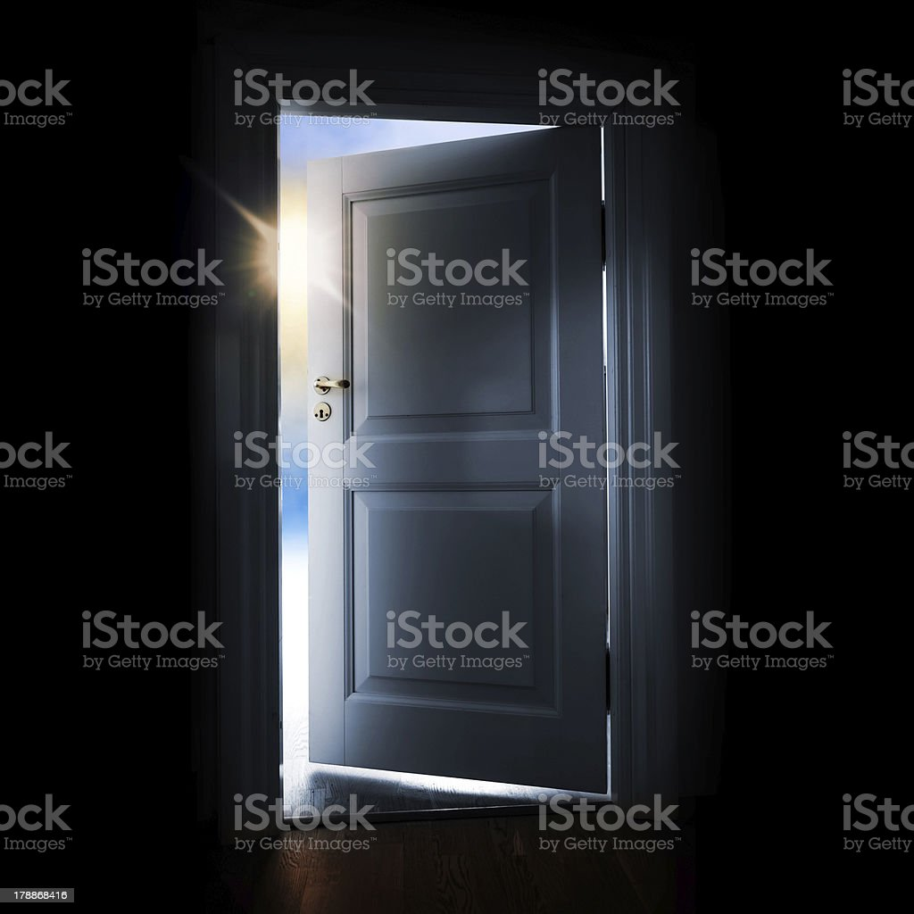 Opening white door in a dark room with light outside stock photo