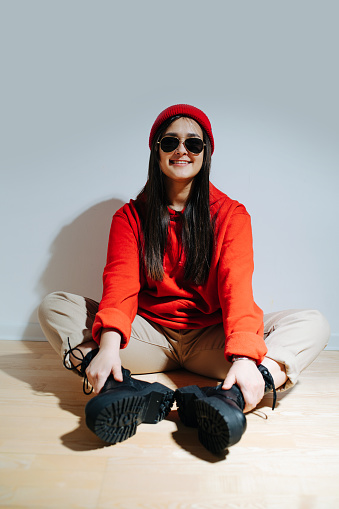 Openly smiling fashionable woman in vibrant red cap and hoodie sitting on floor