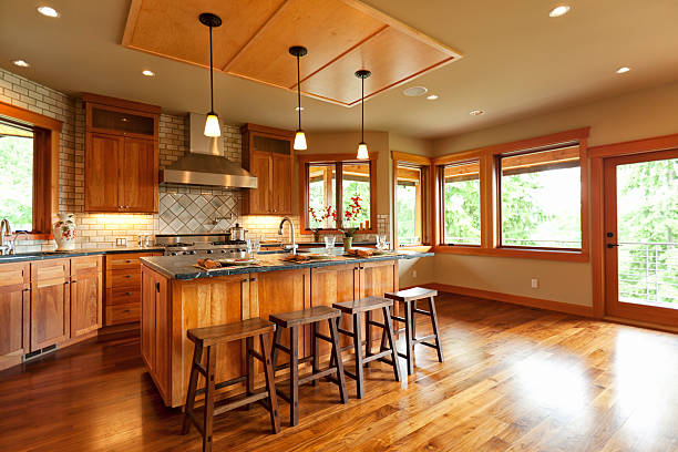 wood floors in kitchen with wood cabinets.  Open plan kitchen with wooden cabinets and walnut floor stock photo Wood Laminate Flooring Pictures Images Stock Photos iStock