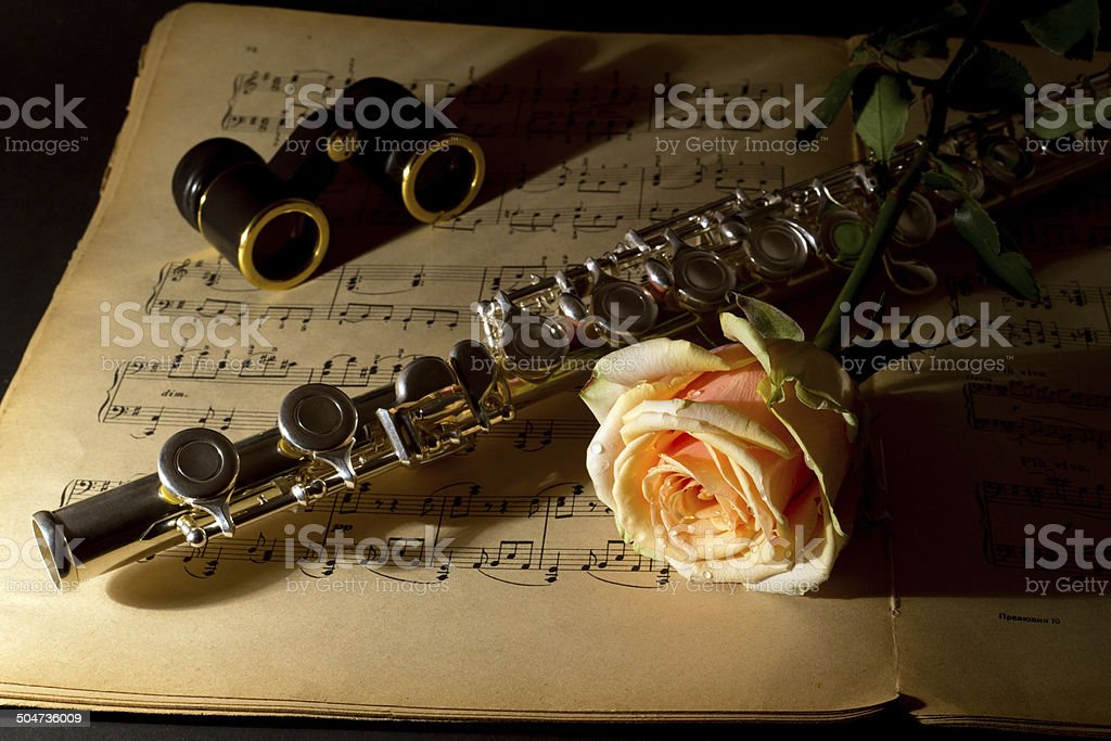 Opera Glasses, Silver Flute and Yellow Rose on Music Score stock photo