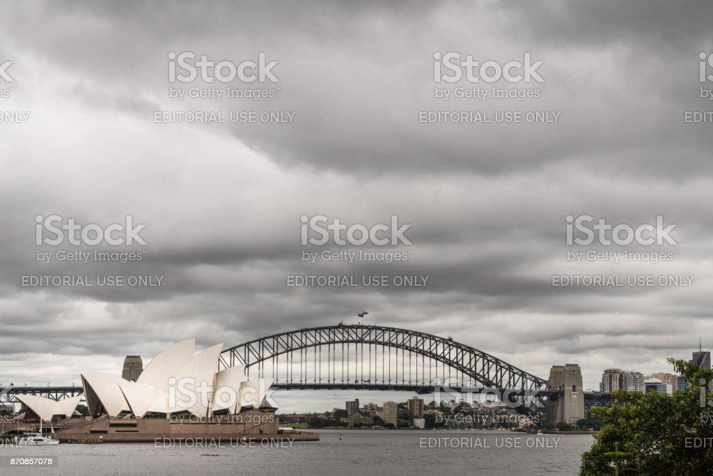 Opera House and Harbour Bridge behind under cloudscape, Sydney Australia. stock photo
