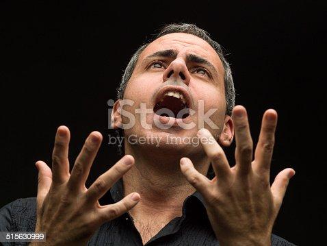 mature man singing opera on black background