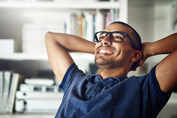 I operate my business as I see fit Cropped shot of a young man looking relaxed in his home office relief emotion stock pictures, royalty-free photos & images